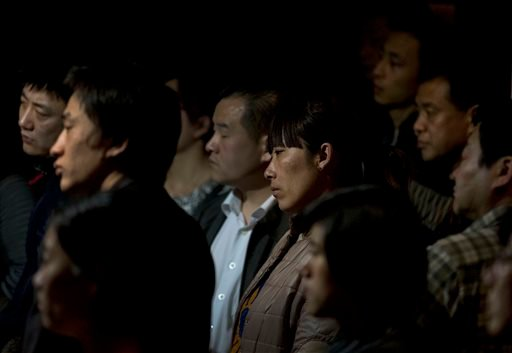 Relatives of Chinese passengers aboard the missing Malaysia Airlines Flight MH370 watch a TV news program about the plane as they wait for a news briefing held by the airlines' officials at a hotel ballroom in Beijing Monday, March 17, 2014. (AP)