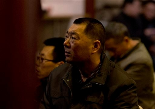 Relatives of Chinese passengers aboard the missing Malaysia Airlines Flight MH370 watch a TV news program about the plane as they wait for a news briefing by the Airlines' officials at a hotel ballroom in Beijing, China, Tuesday, March 18, 2014.