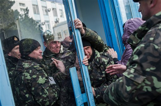 Pro-Russian self-defense force members get through an entrance to the Ukrainian Navy headquarters in Sevastopol, Crimea, Wednesday, March 19, 2014. (AP Photo/Andrew Lubimov)