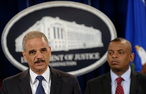 Attorney General Eric Holder, left, accompanied by Transportation Secretary Anthony Foxx, announces a $1.2 billion settlement with Toyota over its disclosure of safety problems, Wednesday, March 19, 2014. (AP Photo/Susan Walsh)