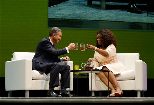 Howard Schultz, left, chairman and CEO of Starbucks Coffee Company, clinks tea cups with Oprah Winfrey, right, to announce their partnership to offer Teavana Oprah Chai tea, Wednesday, March 19, 2014, at Starbucks' annual shareholders meeting in Seattle.