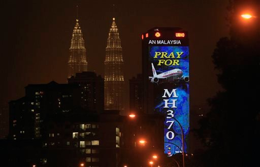 """An office building is illuminated with LED lights displaying """"Pray for MH370"""" next to Malaysia's landmark Petronas Twin Towers in Kuala Lumpur, Malaysia, Wednesday, March 19, 2014. (AP)"""