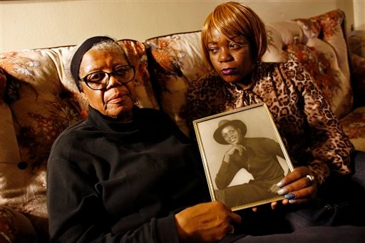In this March 12, 2014 photo, Alma Murdough and her daughter Cheryl Warner hold a photo of Murdough's son, at her home in the Queens borough of New York.