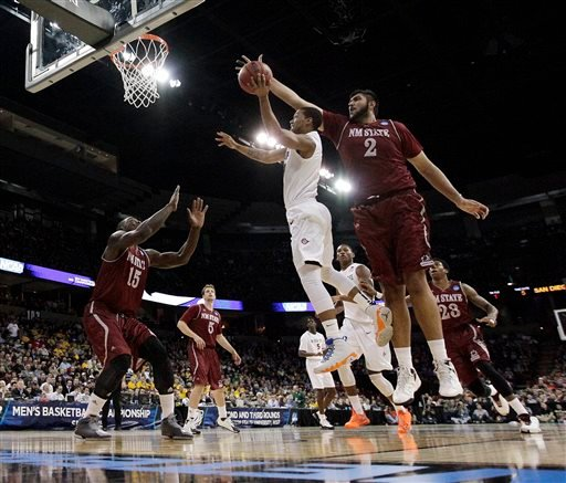 San Diego State's Aqeel Quinn, center, shoots against New Mexico State's Sim Bhullar (2) during the first half of a second-round game of the NCAA men's college basketball tournament in Spokane, Wash.