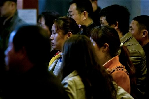 Relatives of Chinese passengers aboard missing Malaysia Airlines Flight MH370 watch a TV news program about the missing flight after they attended a briefing meeting with Malaysian officials in a hotel ballroom in Beijing, China, Friday, March 21, 2014.