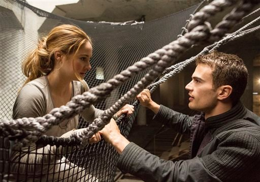 "This image released by Summit Entertainment shows Shailene Woodley, left, and Theo James in a scene from ""Divergent."" The movie releases on Friday, March 21, 2014. (AP Photo/Summit Entertainment, Jaap Buitendijk, file)"