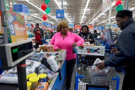 In this Wednesday, Dec. 4, 2013, file photo, April Taylor of Upper Marlboro, Md., left, buys items from groceries to Christmas presents with her son Jarhon Taylor, right, on opening day of a new Wal-Mart on Georgia Avenue Northwest in Washington.
