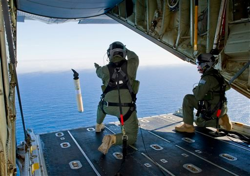 In this photo provided by the Australia Defence Department March 20, 2014, Royal Australian Air Force Loadmasters Sgt. Adam Roberts, left, and Flight Sgt. John Mancey, launch a Self Locating Data Marker Buoy from a C-130J Hercules aircraft. (AP)