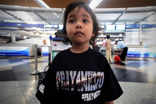 Aisyah Marissa Nurhisyam, 4, wearing a T-shirt printing with messages for the missing Malaysia Airlines, flight MH370, poses for a photo at Kuala Lumpur International Airport in Sepang, Malaysia, Saturday, March 22, 2014.
