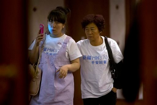 "Relatives of Chinese passengers aboard the missing Malaysia Airlines, MH370, walk out from a meeting room in a hotel wearing a t-shirt which reads ""Pray for MH370 safe return"" in Beijing, China, Sunday, March 23, 2014."