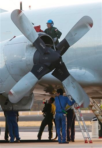 Technicians maintain engines on a Japan Maritime Self-Defense Force P-3C Orion after its arrival to help with search operations for the missing Malaysia Airlines Flight MH370 at Royal Australian Air Force Pearce Base in Perth, Australia, Sunday.