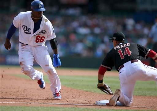 Los Angeles Dodgers' Yasiel Puig, left, is about to be tagged out at third base by the Diamondbacks' Marin Prado during the second game of the two-game Major League Baseball opening series between the Los Angeles Dodgers and Arizona Diamondbacks.