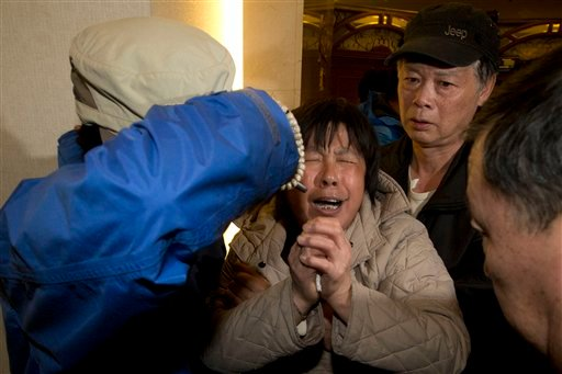 A relative of Chinese passengers aboard the Malaysia Airlines MH370, cries after being told the latest update in Beijing, China, Monday, March 24, 2014.