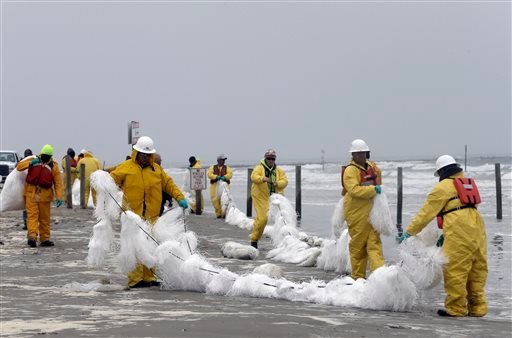 A crew spreads a viscous snare along East Beach to trap oil Monday, March 24, 2014, in Galveston, Texas.