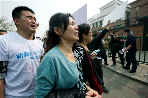 Relatives of Chinese passengers onboard Malaysia Airlines Flight 370 cry as they protest outside the Malaysian Embassy in Beijing, China, Tuesday, March 25, 2014.