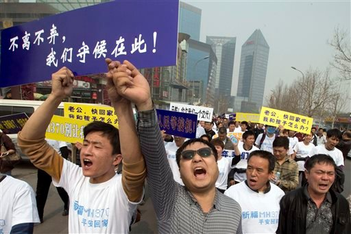 Chinese relatives of passengers onboard the missing Malaysia Airlines plane, flight MH370, shout in protest as they march towards the Malaysia embassy in Beijing, China, Tuesday, March 25, 2014.
