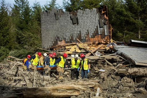 Rescue workers remove a body from the wreckage of homes destroyed by Saturday's mudslide near Oso, Wash, on Monday, March 24, 2014. (AP)