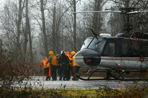 A helicopter and waiting ground crew transfer a worker injured working on the mudslide into a waiting ambulance from a Snohomish County helicopter near Oso, Wash., Tuesday, March 25, 2014.(AP Photo/The Herald, Mark Mulligan)