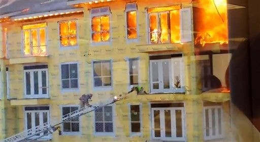 In this image taken from video provided by Karen Jones, a worker reaches for an extension ladder to escape a raging fire as firefighters battle a five-alarm blaze at a construction site Tuesday, March 25, 2014, in Houston. (AP)