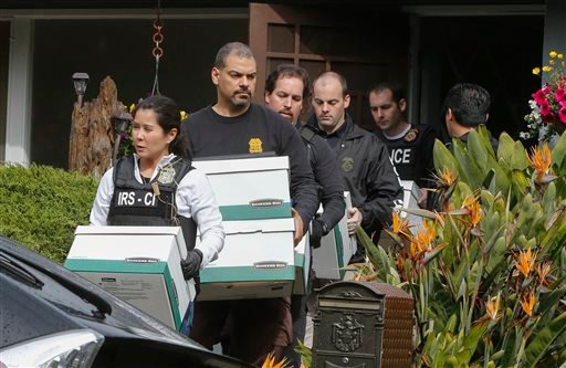 Agents from the FBI and the IRS carry boxes from a home in San Mateo, Calif., on Wednesday, March 26, 2014. (AP)