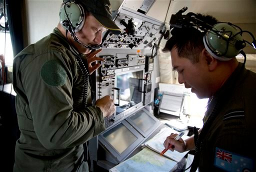 Crew members aboard a Royal Australian Air Force AP-3C Orion aircraft observe navigation maps as they search for missing Malaysian Airlines flight MH370. (AP Photo/Michael Martina, Pool)