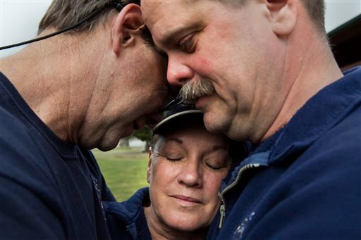 Darrington Fire District 24 volunteer firefighters, Jeff McClelland, left, Jan McClelland, center, and Eric Finzimer embrace each other Wednesday, March 26, 2014, in Darrington, Wash. (AP Photo/The Seattle Times, Marcus Yam)