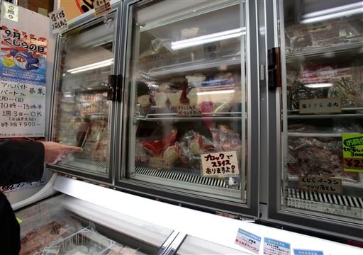 A shopper points at packed whale meat in a freezer at a whale meat specialty store at Tokyo's Ameyoko shopping district, Thursday, March 27, 2014. (AP Photo/Shizuo Kambayashi)