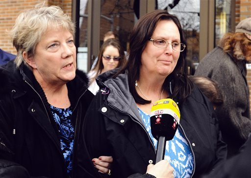 Cody Johnson's mother, Sherry Johnson, right, leaves the federal courthouse with her sister-in-law Celeste Watson, in Missoula, Mont., Thursday, March 27, 2014. (AP Photo/The Missoulian, Michael Gallacher)