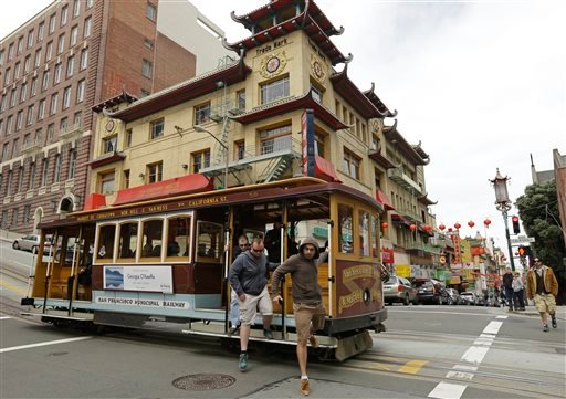 Passengers disembark a cable car in the Chinatown district Thursday, March 27, 2014, in San Francisco. (AP Photo/Ben Margot)