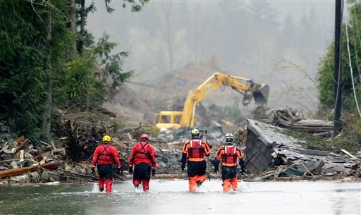Four search and rescue workers wade through water covering Washington Highway 530 Thursday, March 27, 2014. (AP Photo/Ted S. Warren, Pool)