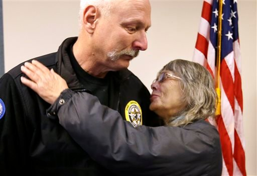 In this March 26, 2014 file photo, Robin Youngblood, right, smiles after embracing Snohomish County helicopter crew chief Randy Fay. (AP Photo/Elaine Thompson, File)