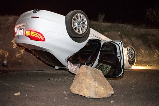 A car sits overturned on a highway in the Carbon Canyon area of Brea, Calif., Friday night, March 28, 2014, after hitting a rock slide caused by an earthquake.
