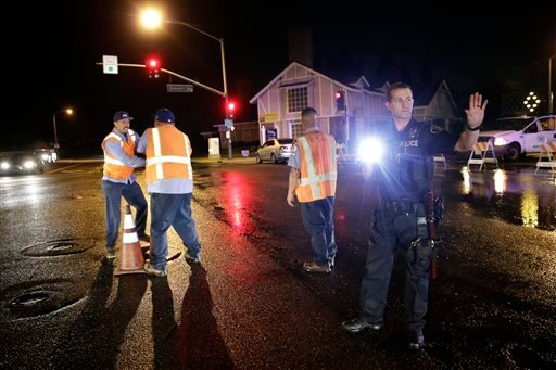A police officer controls the traffic as workers shut off the water valve on Friday, March 28, 2014, in Fullerton, Calif.