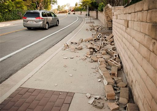 A broken block wall blocks the sidewalk Saturday, March 29, 2014, after an earthquake hit Orange County Friday night in Fullerton, Calif.