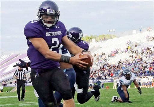 "In this Sept. 21, 2013, file photo, Northwestern quarterback Kain Colter (2), wears APU for ""All Players United"" on wrist tape as he scores a touchdown during an NCAA college football game against Maine in Evanston, Ill."
