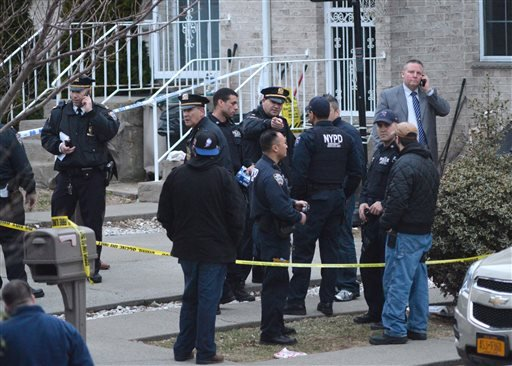 New York City Police gather at the scene as they investigate a triple shooting in the Rosebank section of the Staten Island borough of New York, Friday, March 28, 2014.