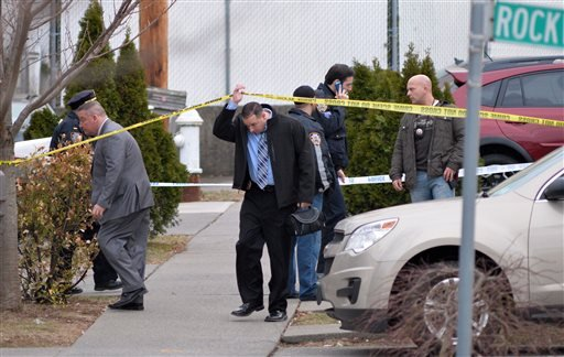 A detective passes under crime scene tape as New York City Police investigate the scene of a double shooting in the Rosebank section of the Staten Island borough of New York, Friday, March 28, 2014.