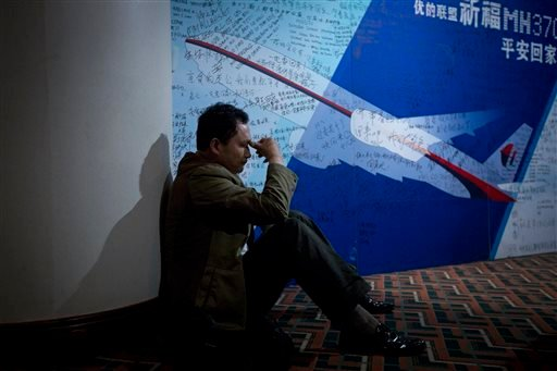 A man, one of the relatives of Chinese passengers onboard Malaysia Airlines Flight 370, rests near a board covered with written wishes at a hotel in Beijing, China, Saturday, March 29, 2014.