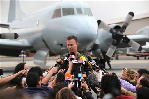 Royal Australian Air Force (RAAF) pilot Flight Lt. Russell Adams speaks to the media his AP-3C Orion returned from searching for debris or wreckage of the missing Malaysia Airlines Flight MH370 in Perth, Australia, Saturday, March 29, 2014.