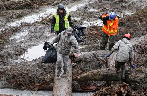 Searchers carry bags of personal belongings collected at the scene of a deadly mudslide Saturday, March 29, 2014, in Oso, Wash.