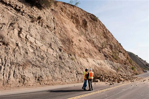 A CalTrans worker and a geologist look at a rock wall where a rockslide closed Carbon Canyon Road near Carbon Canyon Regional Park in Brea, Calif., on Saturday, March 29, 2014 after an earthquake hit Orange County Friday night.