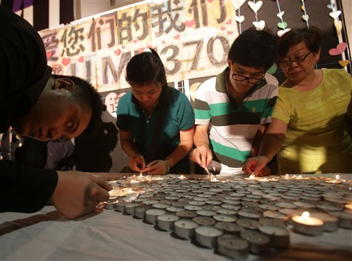 People light candles during a ceremony for the passengers on board the missing Malaysia Airlines flight MH370 in Kuala Lumpur, Malaysia, Sunday March 30, 2014.