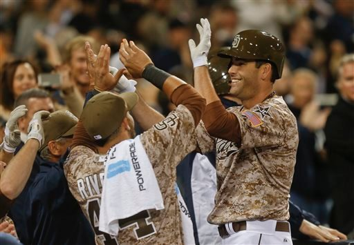 San Diego Padres Seth Smith is greeted at the dugout after his game tieing home run against the Los Angeles Dodgers in the eighth inning of the opening game of Major League baseball in the United States Sunday, March 30, 2014, in San Diego.