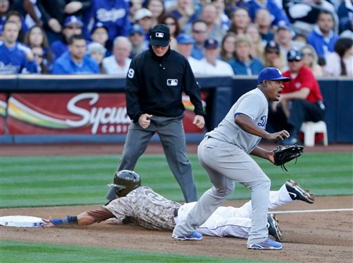 San Diego Padres' Everth Cabrera slides into third safely as Los Angeles Dodgers third baseman Juan Uribe awaits a late throw in the first inning of the opening game of Major League baseball in the United States Sunday, March 30, 2014, in San Diego.