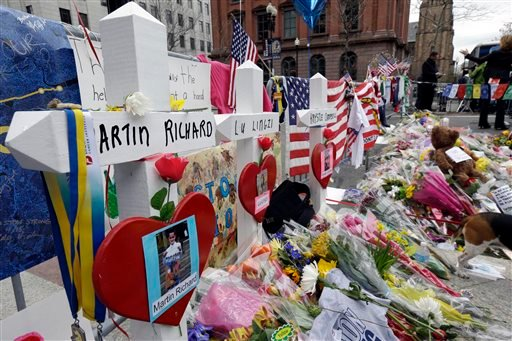 In this April 18, 2013 photo, memorials for Martin Richard, Lingzi Lu, and Krystle Campbell, killed in the bombings near the finish line of the Boston Marathon, stand among other artifacts at a makeshift memorial in Copley Square in Boston.