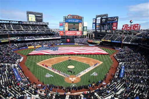A giant American flag is unfurled before a baseball game between the New York Mets and Washington Nationals on opening day at Citi Field, Monday, March 31, 2014, in New York. (AP Photo/John Minchillo)