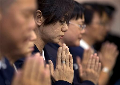 Volunteers from Taiwan's Buddhist association offer prayers for the Chinese passengers aboard the missing Malaysia Airlines flight MH370, at a hotel in Beijing, China Tuesday, April 1, 2014.
