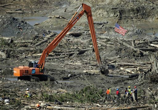 A group of workers stands near a long-arm excavator and a U.S. flag Tuesday, April 1, 2014, near Darrington, Wash., as work continued to search for victims of the deadly mudslide that hit the community of Oso,Wash. on March 22, 2014. (AP)