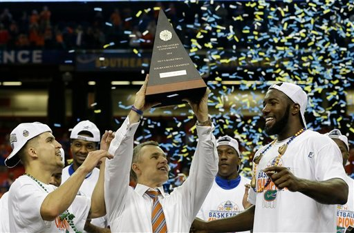 Florida head coach Billy Donovan holds the SEC championship trophy after the second half of an NCAA college basketball game against Kentucky in the Championship round of the Southeastern Conference men's tournament, Sunday, March 16, 2014, in Atlanta.