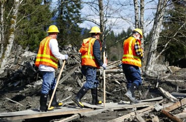 Washington State Department of Transportation workers enter the mudslide site on a constructed path of plywood on Highway 530 near mile marker 37, near Oso, Wash., Tuesday, April 1, 2014. (AP Photo/The Seattle Times, Lindsey Wasson)
